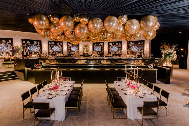 Corporate dinner party with lavish gold balloon ceiling installation.