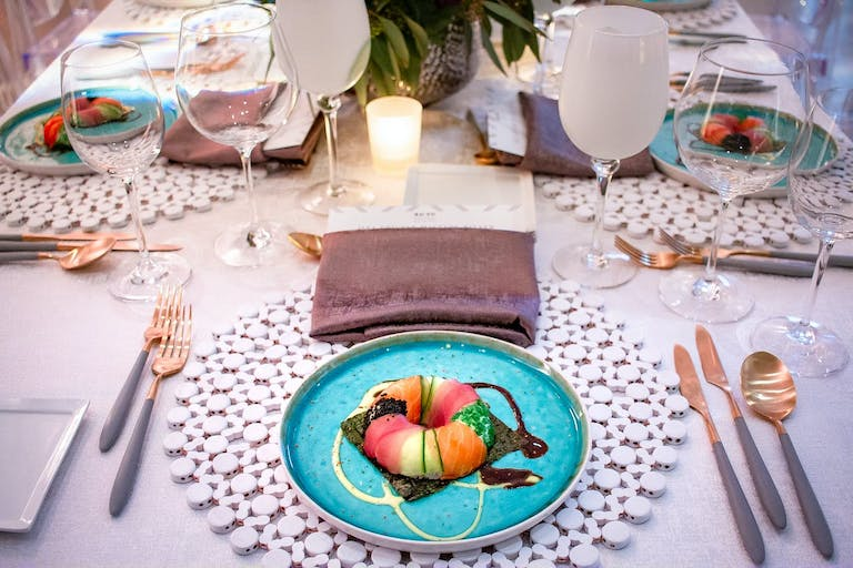 Corporate dinner party with colorful dishware and artistic food presentations.