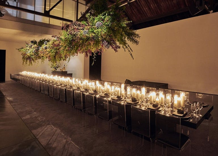 Candlelit corporate dinner party in modern studio space.