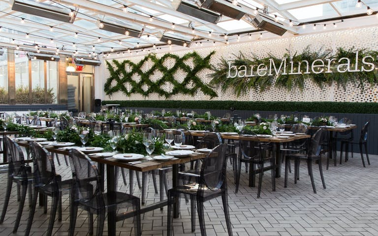 bareMinerals corporate dinner party with lots of greenery and branded signage.