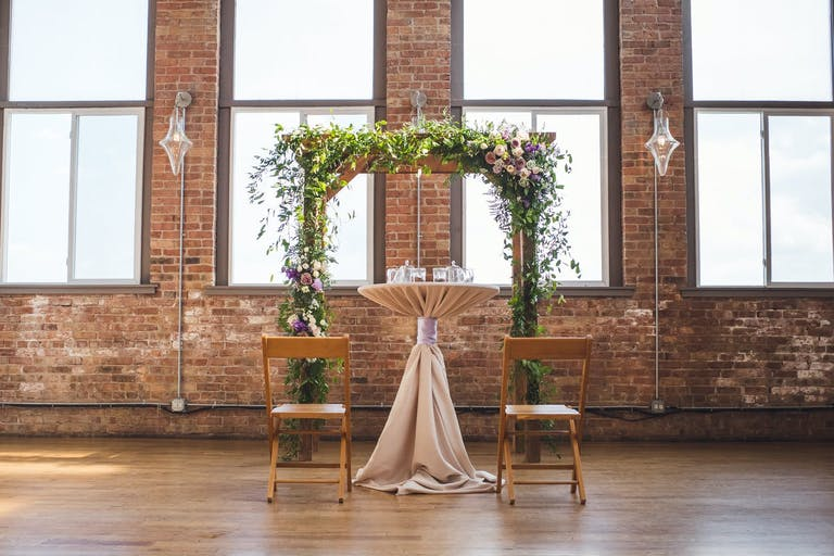 Modern and rustic wedding arch in industrial loft space.