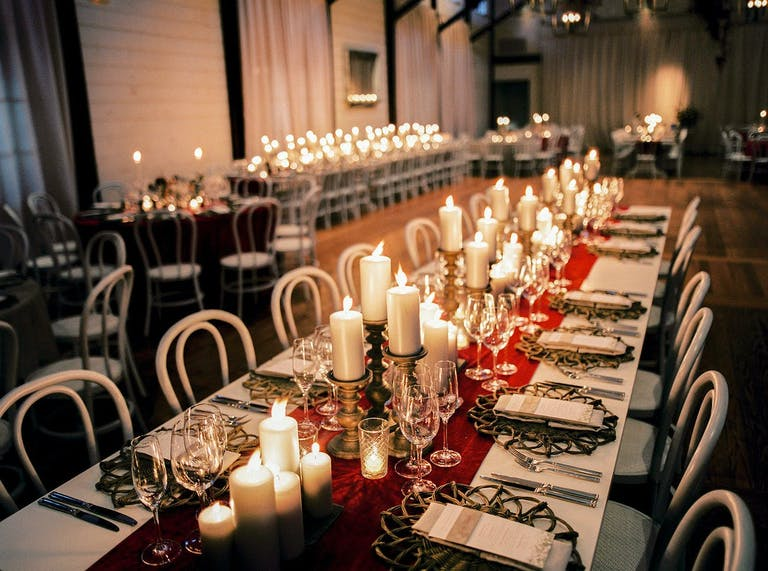 Rustic wedding reception table with candlelight and crimson table runner.