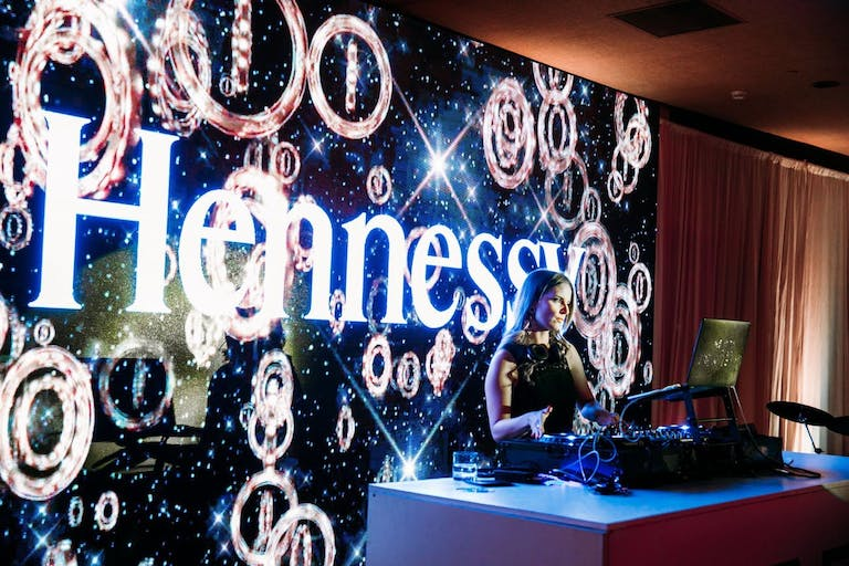 Hennessy corporate dinner party with DJ and branded décor.