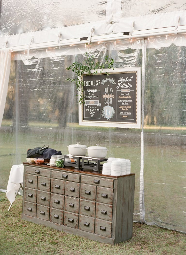 Rustic wedding catering station with vintage dresser.