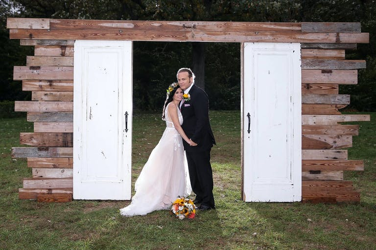 Rustic wedding backdrop featuring white country doors and beams of wood.