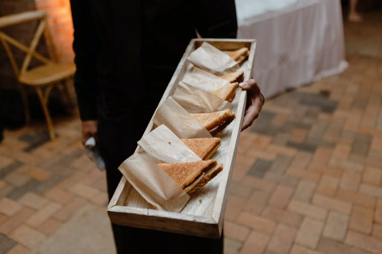 Wedding passed plates of individually-wrapped grilled cheese.
