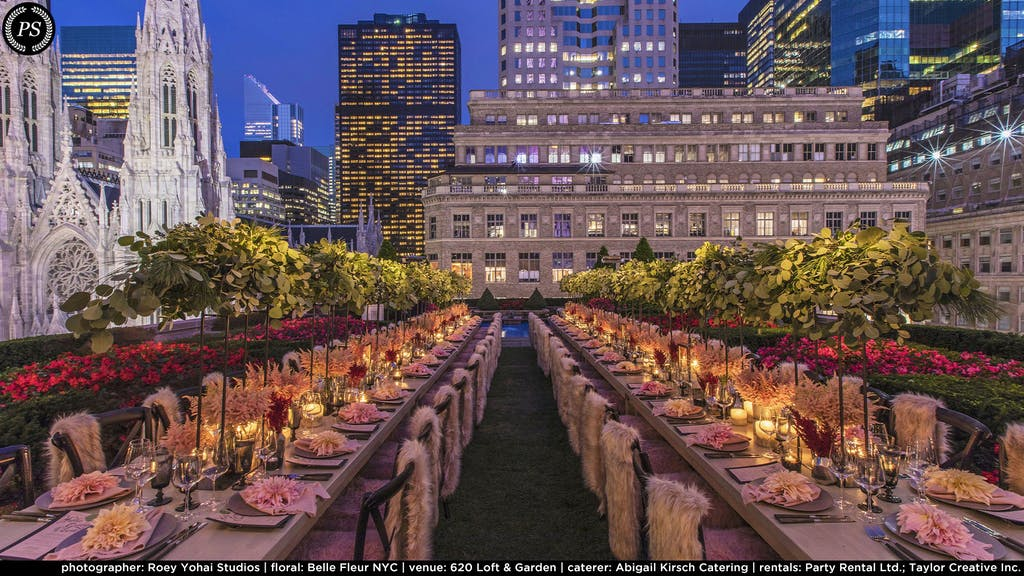 two long tables with raised greenery as the centerpiece and glowing candles below. Pink fur chair throws on each setting and a lit skyline in the background.