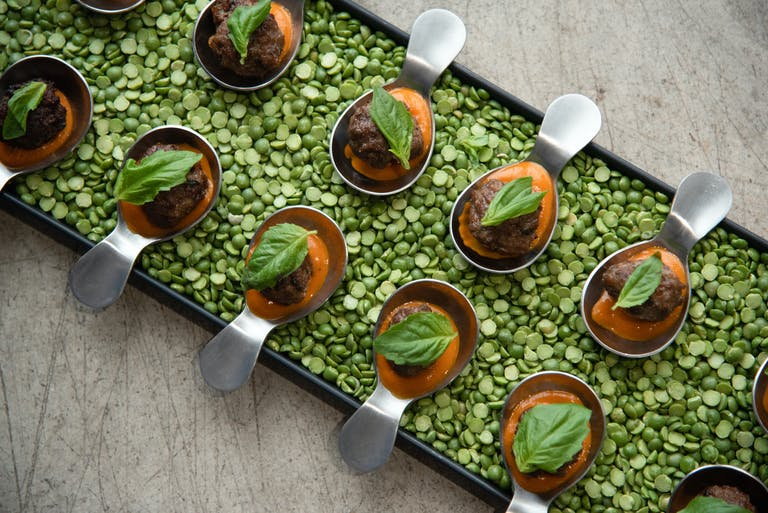 Corporate dinner party with passed appetizer trays filled with dried green peas.
