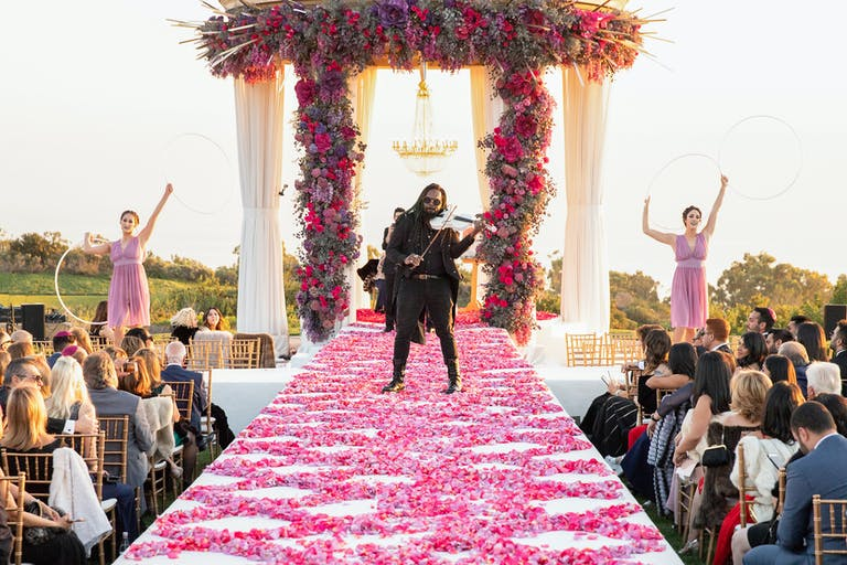 Unique Wedding Idea Where Man Plays Violin in Middle of Pink Petal-Strewn Wedding Aisle | PartySlate