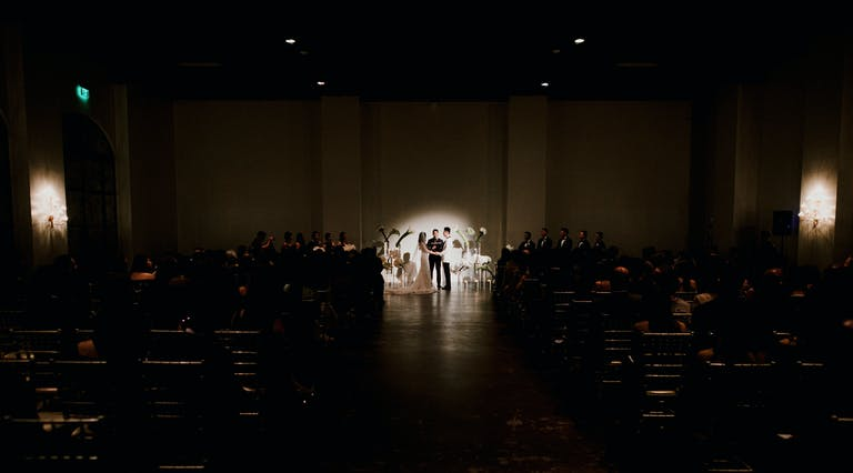 Dimmed Wedding Ceremony With Spotlight Shining on Couple | PartySlate