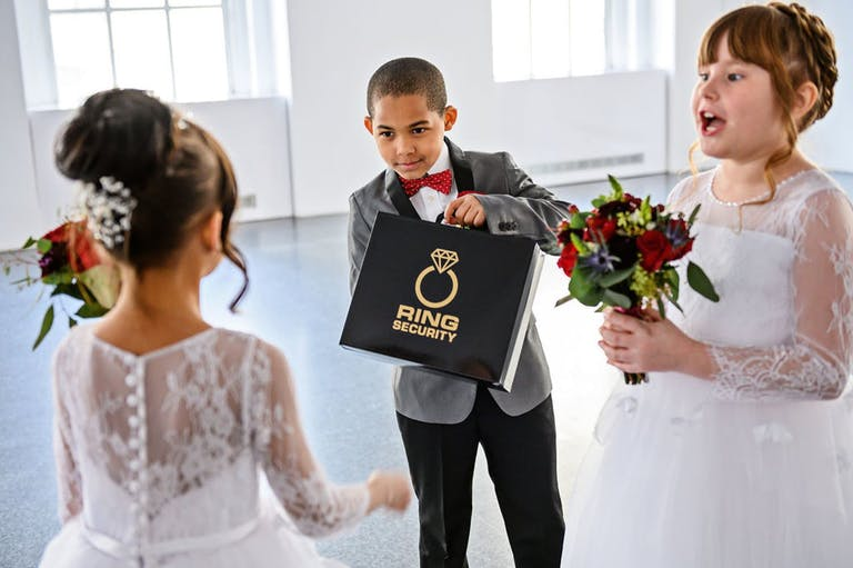 The ring bearer shows off his ring security box to flower girls | PartySlate