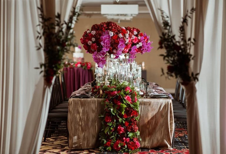 Photo of wedding table with pink orchid centerpieces and overflowing roses and greenery.