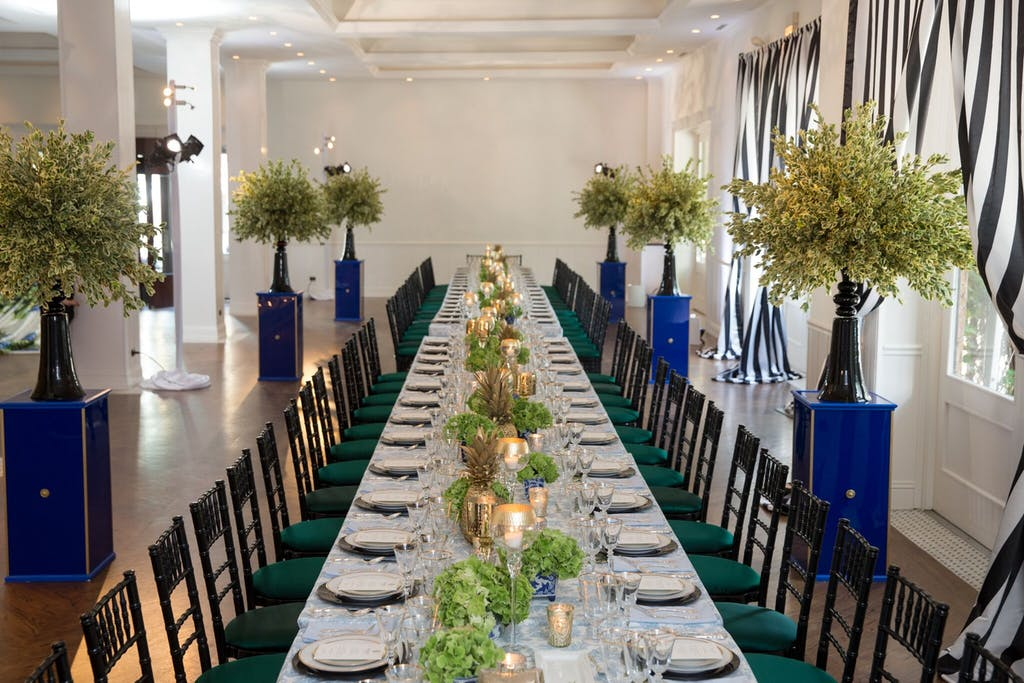 a long table with emerald green chairs on either side and candles and greenery down the middle. White plates and translucent glasses at each place setting and trees on blue pedestals flanking the table.