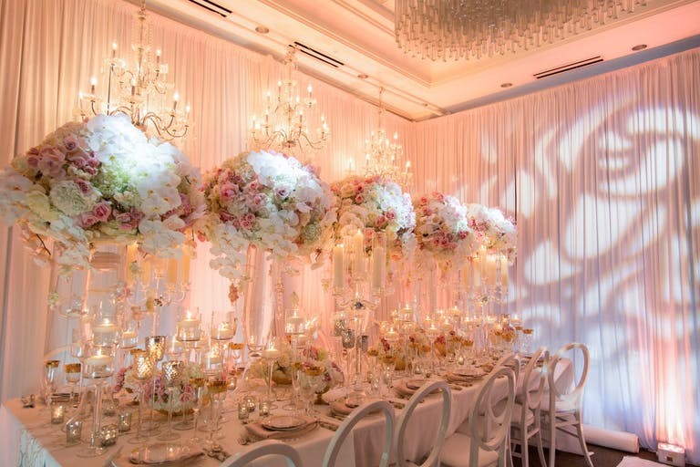 Romantic and ethereal wedding reception with tall floral centerpieces and creative light mapping.