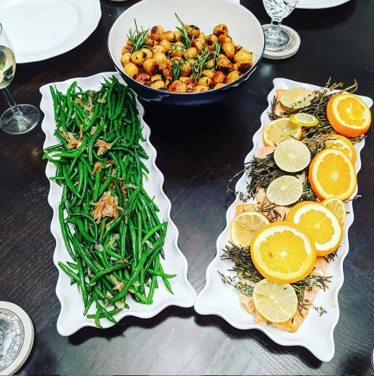 Catered salmon with lemons, green beans, and potatoes.