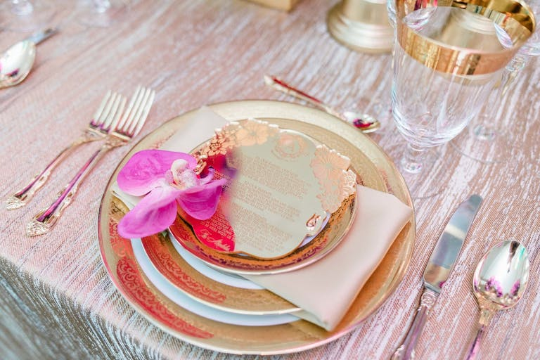 Dinner plate with pink orchid and artfully designed menu.