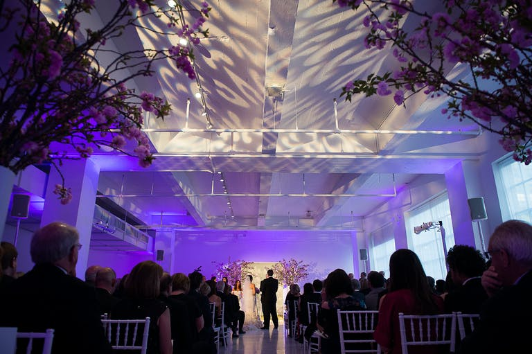 Wedding Ceremony With Shadows and Light Displayed on Ceiling Above Aisle | PartySlate