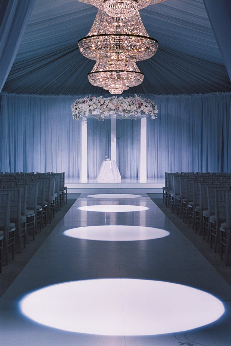 Stunning Tented Wedding with Unique Wedding Aisle Featuring Consecutive Spotlights | PartySlate