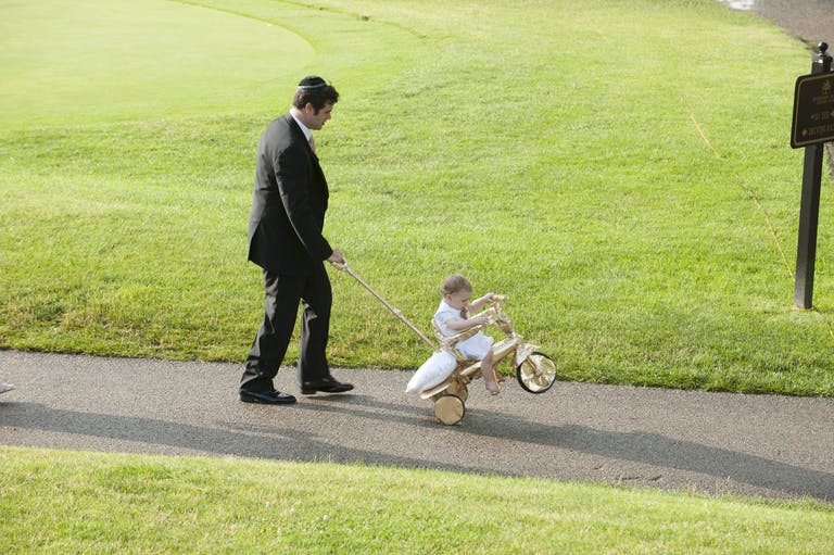 Traditional Jewish Wedding Celebration Where Father Pushes Kid on Bicycle Down Wedding Aisle | PartySlate