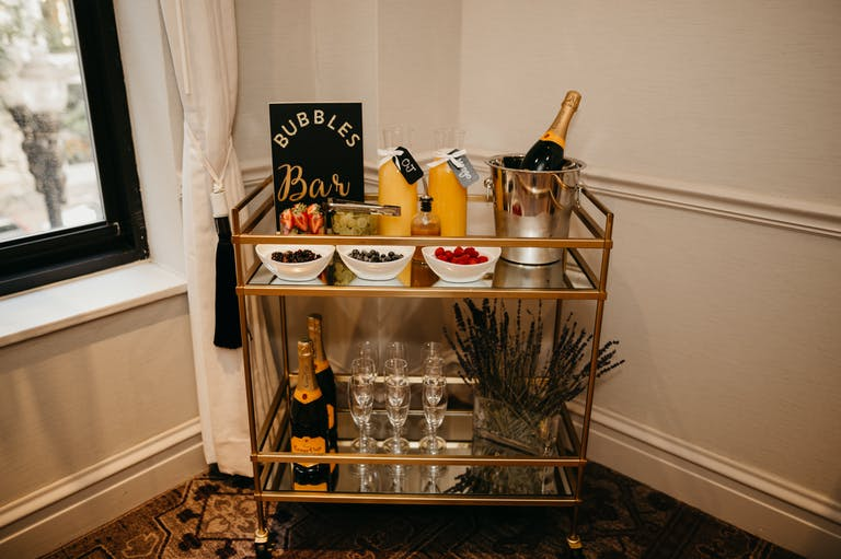 Bubble bar with bar cart filled with champagne and fruits at The Talbott Hotel in Chicago, IL | PartySlate