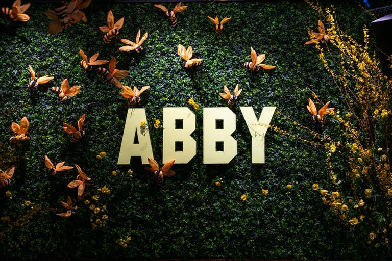 greenery wall with gold lettering and paper bees for photo op | PartySlate