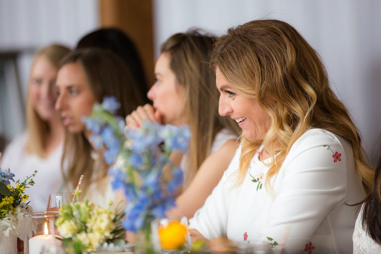 Build Your Own Bouquet Baby Shower women talking across a floral table | PartySlate