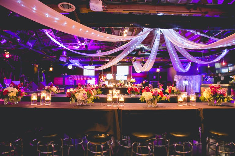 Festive wedding reception with long tables and lite up linen hanging from the ceiling | PartySlate