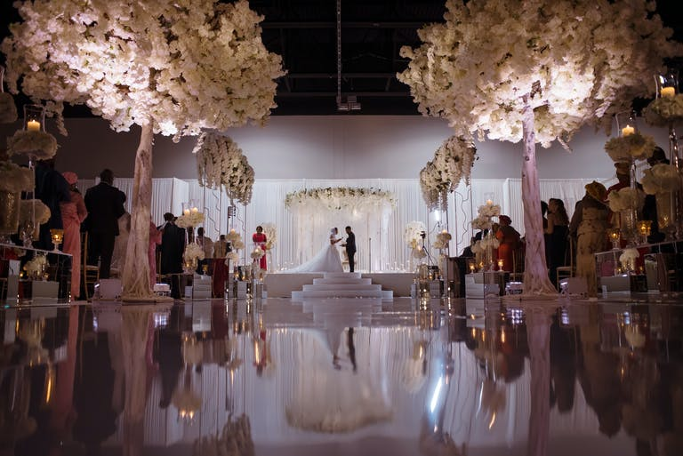Glamorous all-white wedding with white flower trees and a mirrored aisle