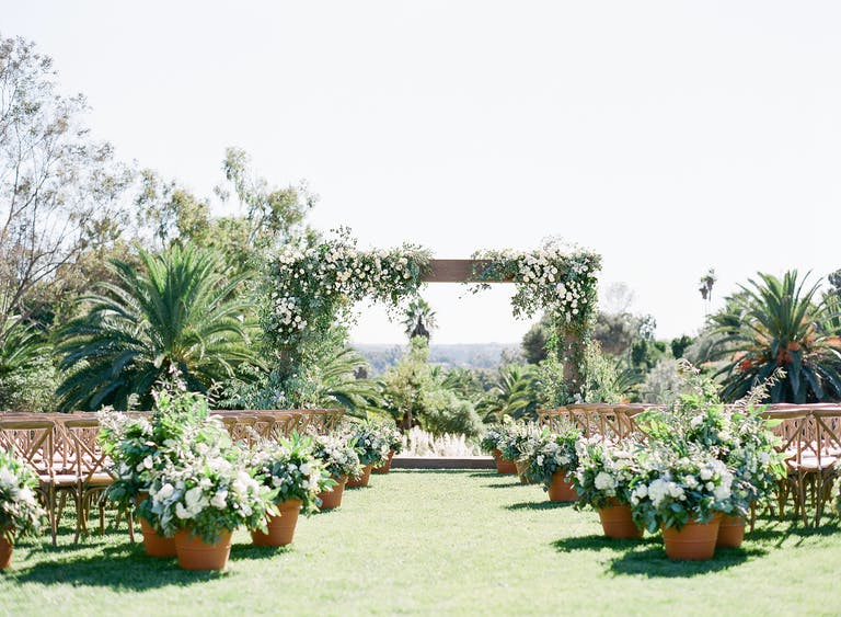 Outdoor wedding aisle with potted plants and natural greenery.