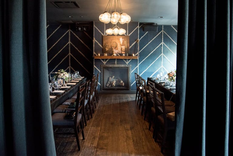 The Devil's Den private room at The Dawson in Chicago with navy and gold wallpaper and wood floors | PartySlate