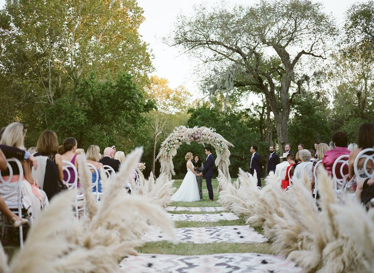 Rustic outdoor wedding with pampas grass and a wedding aisle covered in boho throw rugs.