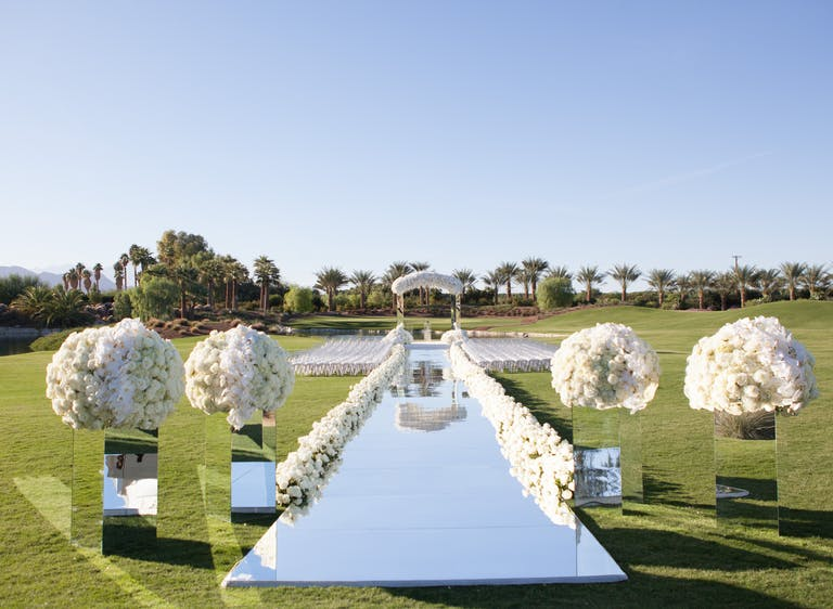 mirrored wedding aisle with white flowers on mirrored bases in a grassy field