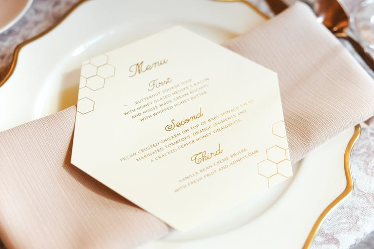 honeycomb shaped dinner menu on blush napkin at luncheon table   PartySlate