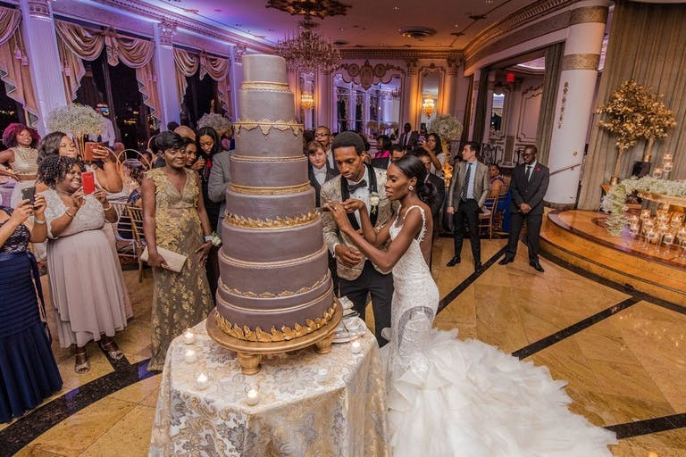 Bride and groom cutting the eight tier wedding cake | PartySlate
