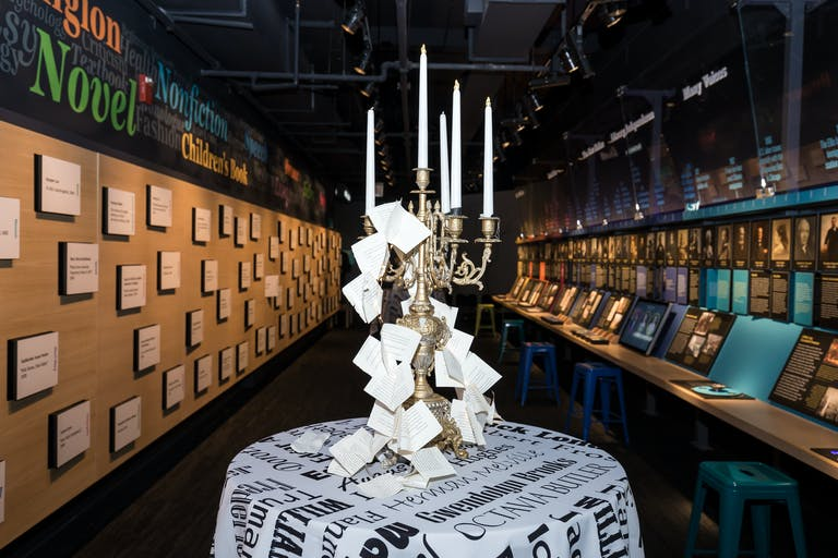 Writers museum Chicago event with large candelabra on a newspaper print tablecoth | PartySlate