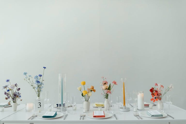 Rainbow inspired floral arrangement on a sleek white table | PartySlate