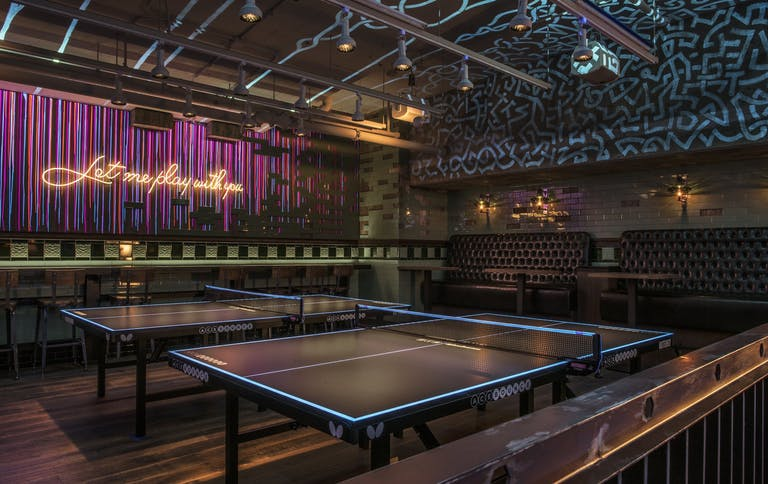 Private event space for your sweet sixteen with ping-pong tables, seating and abstract wall decor | PartySlate