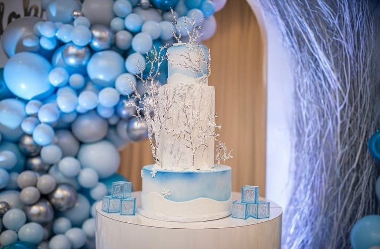 Blue and gray balloon installation and an icy blue tiered cake | PartySlate