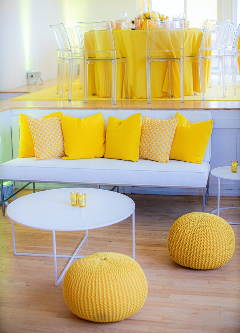 White lounge area and seating tables with yellow accents | PartySlate