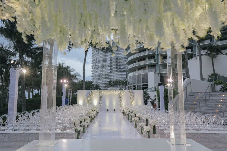 Glass archways at the end of a wedding aisle with white florals overhead | PartySlate