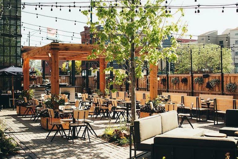 A courtyard rooftop in Chicago with wooden seating and accents with string lights | PartySlate