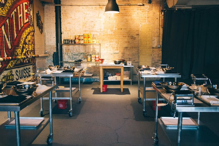 An industrial event space for a sweet 16 cooking class with five tables to cook at | PartySlate