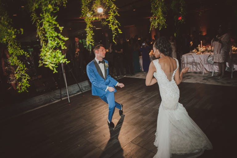 Bride and groom dancing with greenery draping down | PartySlate