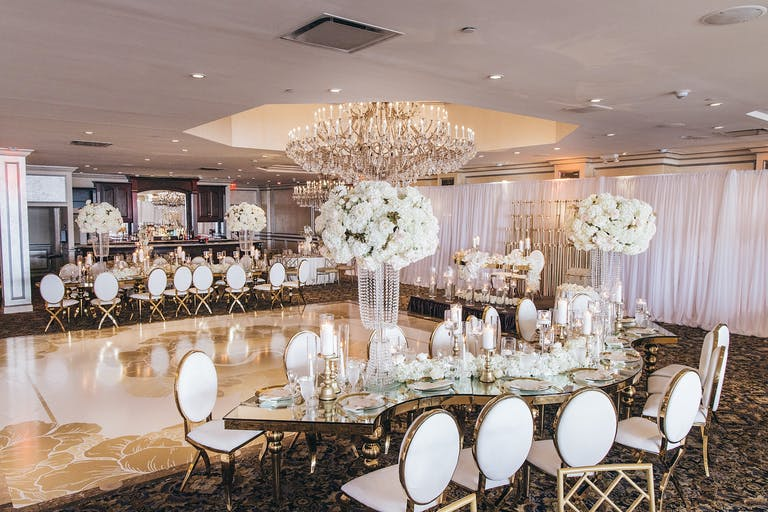 Wedding reception table arrangements with a gold dance floor and white florals | PartySlate