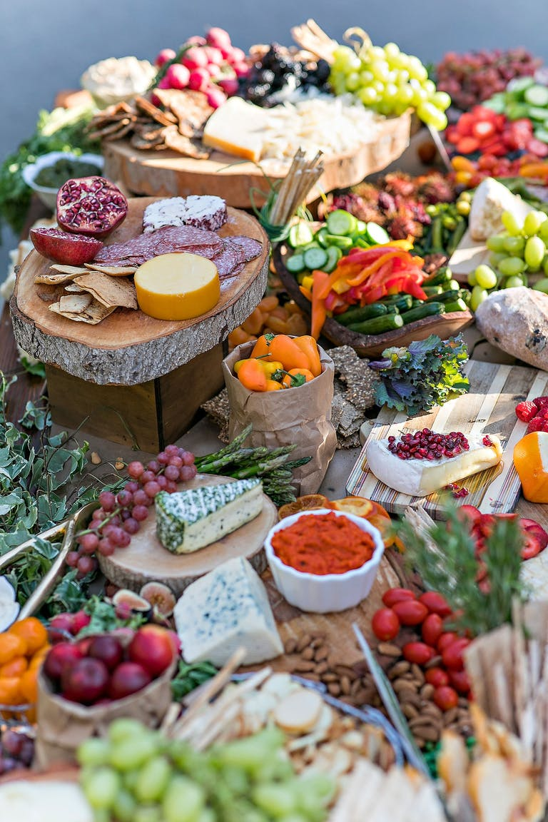 A table covered with wooden trays, piled high with meats, cheese, vegetables, and fruit | PartySlate