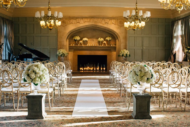 Wedding Ceremony Site with White Hydrangea Aisle Markers and Fireplace Backdrop