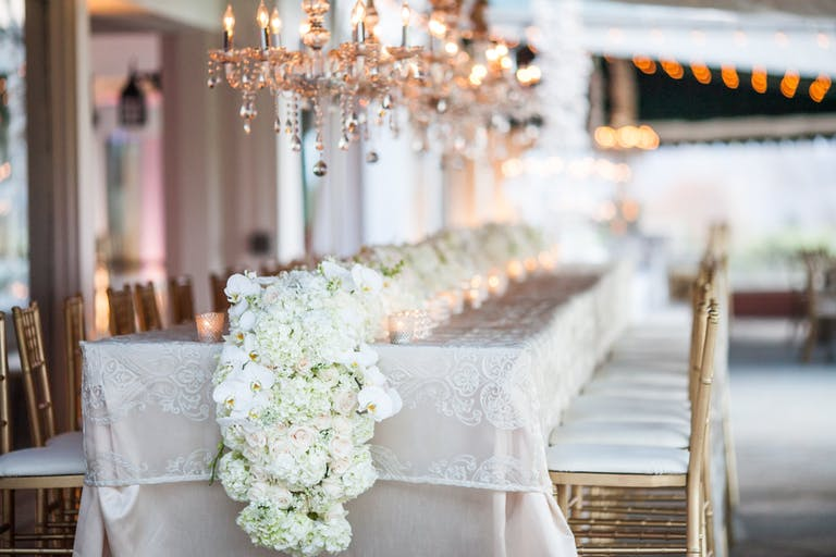 Wedding Reception Table with White Linen, Gold Chairs, and White Hydrangea Wedding Centerpieces