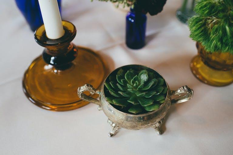 Succulent wedding centerpiece, blue vase ware, and golden candle stick holder.