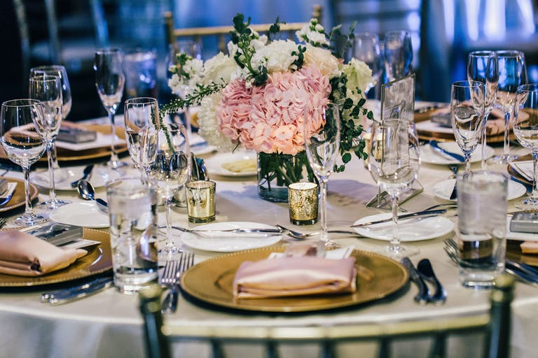 Wedding Table with Pink Hydrangea Wedding Centerpieces, Gold Plates, and Pale-Pink Napkins