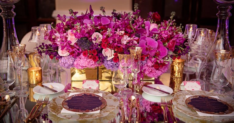 Close Up of Wedding Centerpiece Featuring Purple Hydrangeas, Hot Pink Orchids, and Pale Pink Roses